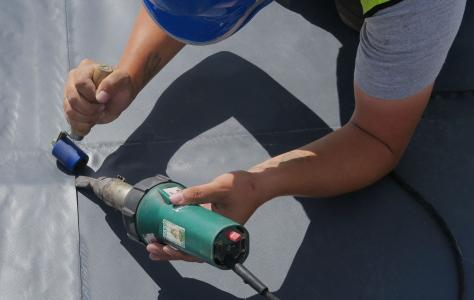 Installer heat welds single ply membrane